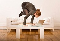 Woman balancing on table with laptop