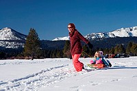 Mature woman pulling her daughters on a sled