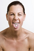 headshot of young woman showing her tongue with pill