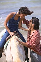 Couple horseriding on beach