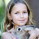 A young girl holding a pet rabbit, close-up