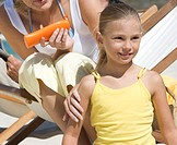 A mother applaying sunscreen on her daughter