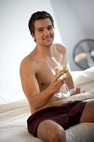 Young man holding two champagne glasses, sitting on a bed