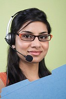 Businesswoman in headset carrying folders