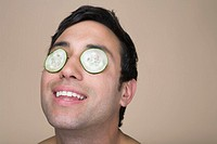 Man wearing cucumbers over eyelids