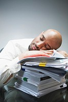 Businessman sleeping on pile of work