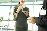 A businesswoman having a cup of coffee with a visiting colleague