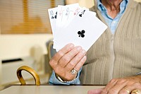 An elderly man playing cards