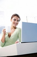 Woman sitting in kitchen, with laptop, holding cup