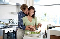 Young couple in kitchen, woman preparing salad
