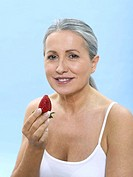Senior woman holding strawberry, portrait