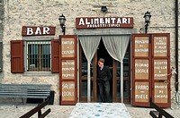 Mature man standing at the entrance of a bar, Umbria, Italy