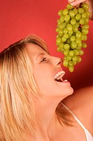 A young woman holding a bunch of grapes to her mouth