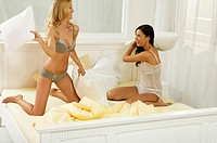 Two young women having a pillow fight in bed