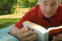 A senior adult reading a book