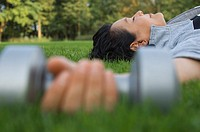 A woman lying down after lifting dumbbells