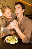 A couple eating salad at a restaurant