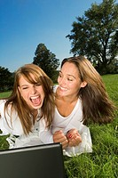 Two friends lying on the grass and using a laptop