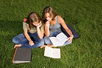 Two teenage girls studying in the park