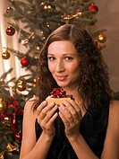 Woman holding a present in front of a Christmas tree