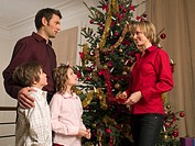A family standing around the Christmas tree