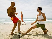 Woman looking at men playing football on the beach