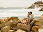 Couple sitting on the rocks at a beach