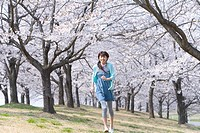 Portrait of a woman running under the cherry trees, smiling, front view, Japan