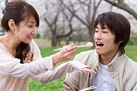 Woman feeding man aroid with chopsticks, smiling, front view, side view, Japan