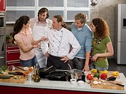 Male Chef teaching four students in the kitchen