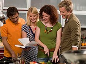 Four people preparing food in the kitchen