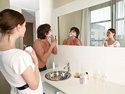 Woman looking at her boyfriend shaving