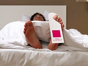 Man sleeping with a do not disturb sign on his toe