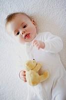 A baby holding a teddy bear