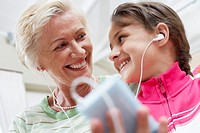 Little Girl Listening to a MP3 Player With Grandmother
