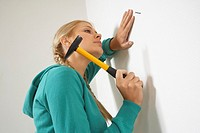 Side profile of a young woman hammering a nail into a wall
