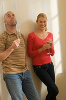 Couple leaning against a wall and holding champagne flutes