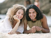 Portrait of a young couple lying on the beach and smiling