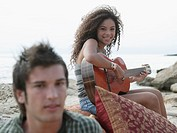 Portrait of a young woman playing the guitar with a young man beside her