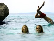 Two young women in the sea with a young man jumping behind them