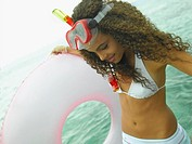 Close-up of a young woman holding a life belt on the beach