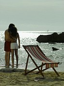 Man and a woman with their arm around each other standing on the beach