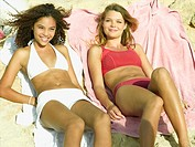 High angle view of two young women lying on beach towels and smiling