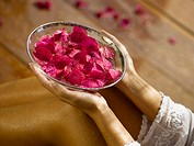 A woman holding a bowl of rose petals