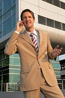 Businessman talking on a mobile phone and smiling (thumbnail)