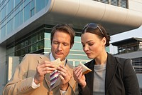 Businessman and a businesswoman eating sandwiches