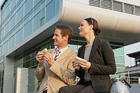 Businessman and a businesswoman holding sandwiches and smiling (thumbnail)