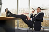 Businessman sitting on an office chair and holding a cigar