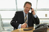 Businessman talking on the telephone and shouting