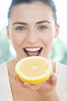 Young woman holding half a grapefruit, mouth open